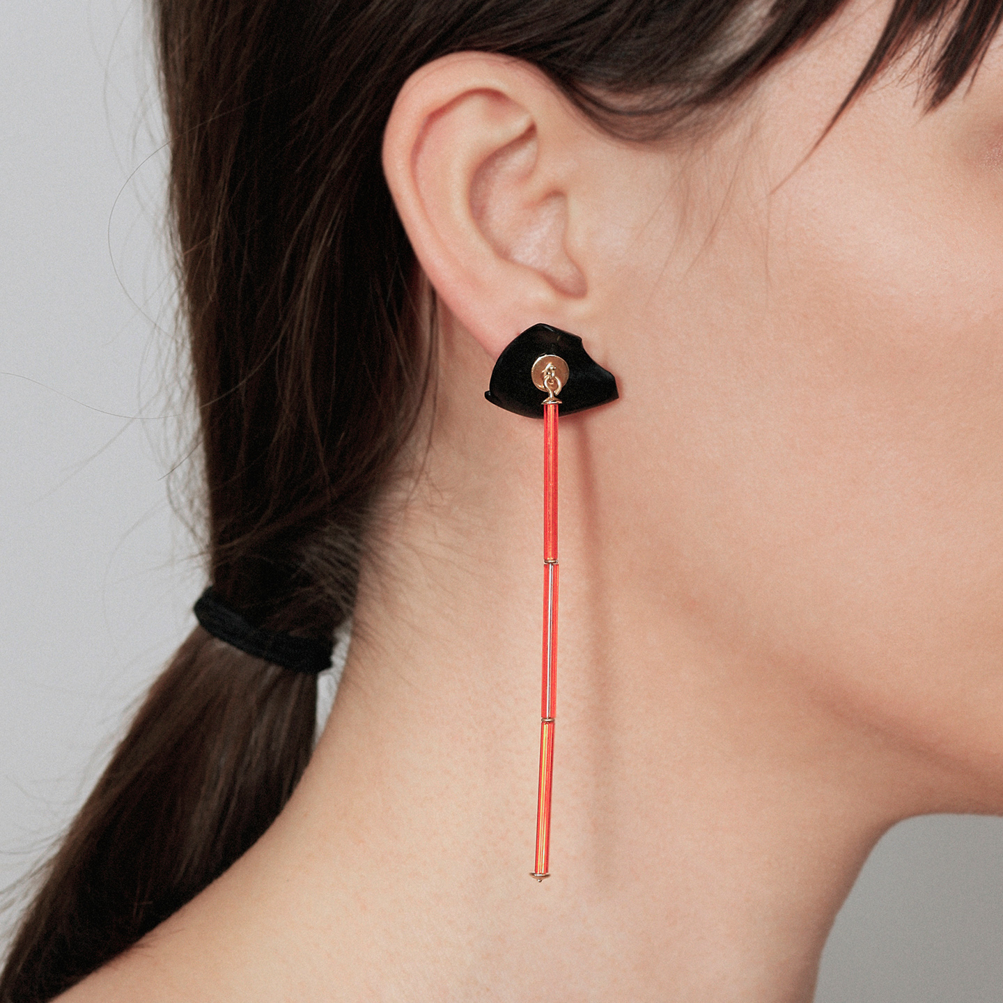 Long gold earring with neon orange bars and false onyx dilation