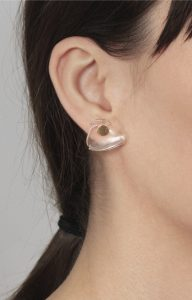 Gold earring with false clear quartz dilation