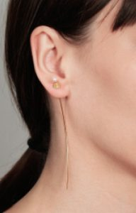 Long gold earring with floating pearl